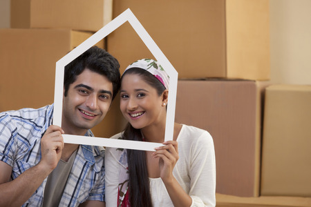 looking through frame: Portrait of smiling young couple looking through a house shaped frame