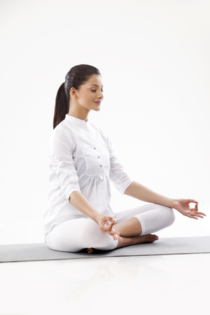 self conscious: Smiling young woman in lotus position