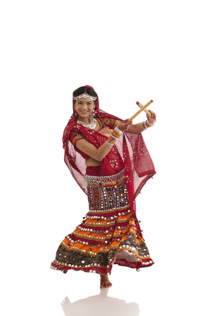 Female dandiya dancer dancing with sticks