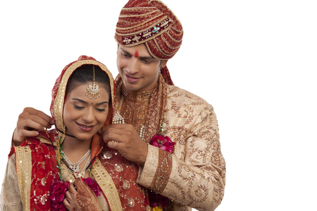 Gujarati groom tying a mangal sutra around brides neck