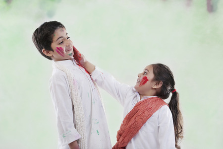 Girl putting colour on a boys face