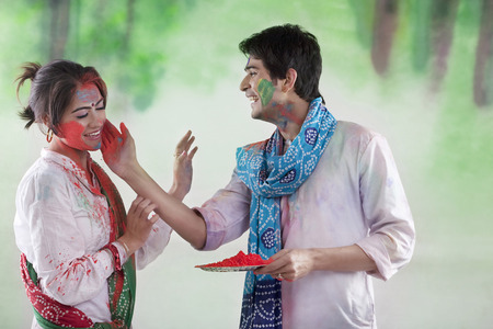 Man putting colour on a womans face