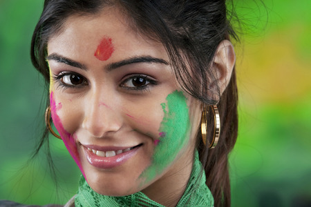 Holi colours on womans face Imagens