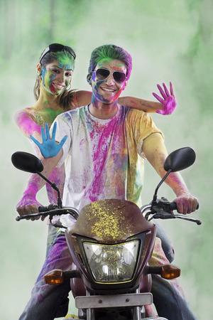 messy clothes: Couple on a motorcycle covered with colours