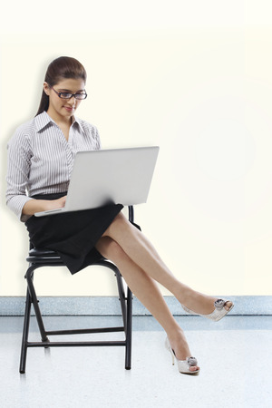 Secretary sitting on a chair with a laptop