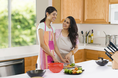 2 50: Mother teaching her daughter to cut vegetables