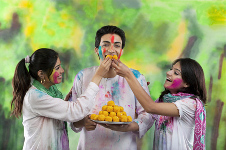 Women feeding a man laddoos