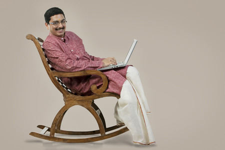 South Indian man on a chair with a laptop