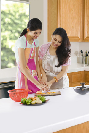 Mother teaching her daughter to cut vegetables