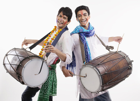 Two men playing on dholaks Imagens
