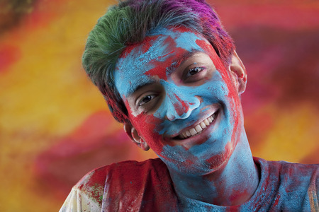 Mans face covered in holi colours Stock Photo