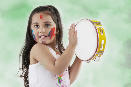 Girl playing on a tambourine Banco de Imagens