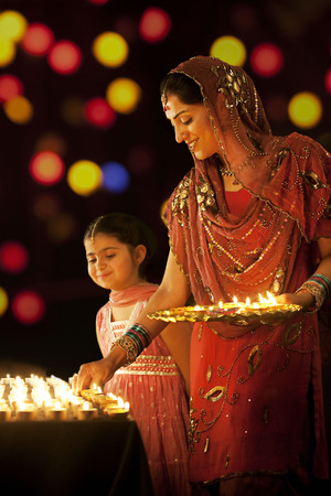 down lights: Mother placing diyas on a table while her daughter looks on