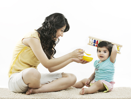 Mother trying to feed her child Stock Photo