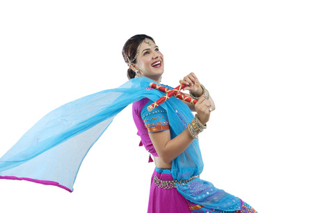 Gujarati woman dancing with dandiya sticks