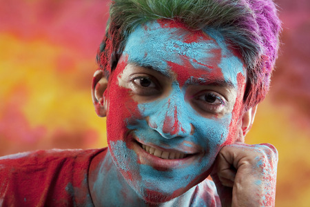 Mans face covered in holi colours Imagens