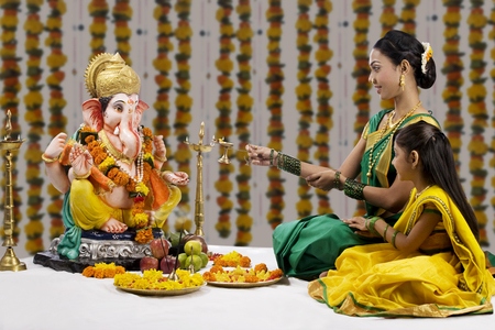 Mother and daughter performing a pooja Stock Photo