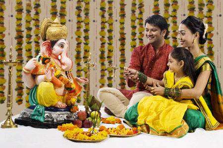 Family performing a pooja Stock Photo - 80551491