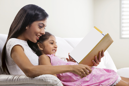 Mother and daughter reading a story book Stock Photo - 80551498