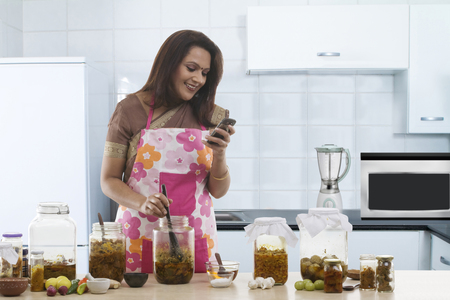 30 35 years: Woman reading an sms while making pickle Stock Photo