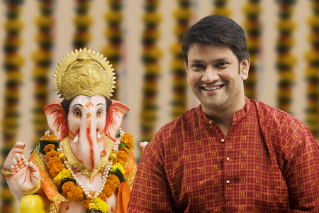 Portrait of a man with a Ganesh idol Stock Photo