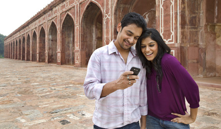Couple reading an sms at Humayuns Tomb Stock Photo