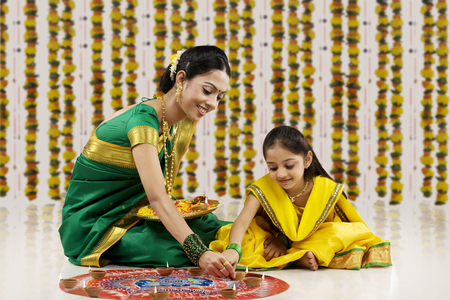 Mother and daughter placing diyas on a rangoli