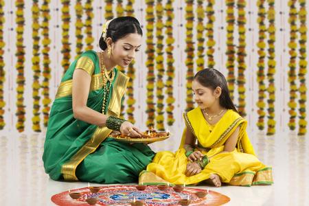 Woman placing diyas on a rangoli