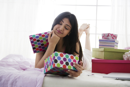 one sheet: Girl looking at the contents of a gift box Stock Photo
