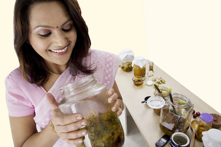 30 35 years: Woman looking into a jar of pickle Stock Photo
