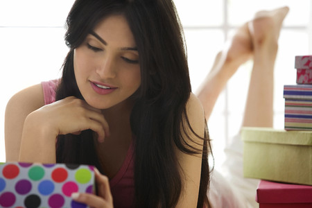 25 30: Girl looking at the contents of a gift box Stock Photo