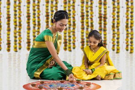 Woman arranging diyas on a rangoli