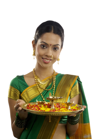 Portrait of a woman holding a tray with diyas Stock Photo