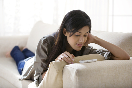 25 30: Young woman watching a video on her mobile phone
