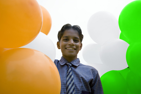 tricoloured: Portrait of a school boy with balloons