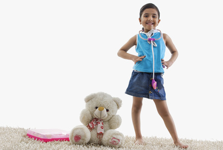 Young girl standing next to her teddy bear
