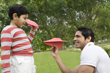 25 30: Father and son having fun with paper airplanes