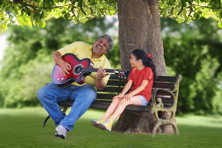 Grootvader die gitaar speelt voor kleindochter