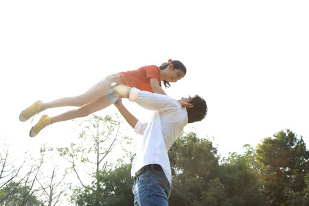 joyfulness: Father lifting his daughter in the air Stock Photo