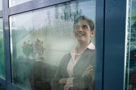 25 30: Businesswoman looking out of a window