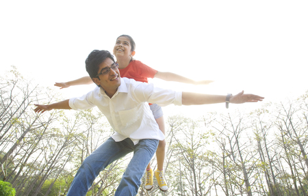 joyfulness: Girl balancing on her fathers back