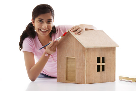 Teenage girl painting a wooden house