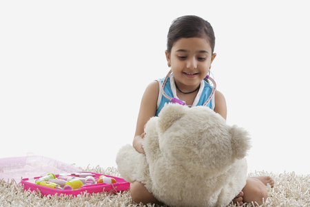 Girl playing doctor with her teddy bear