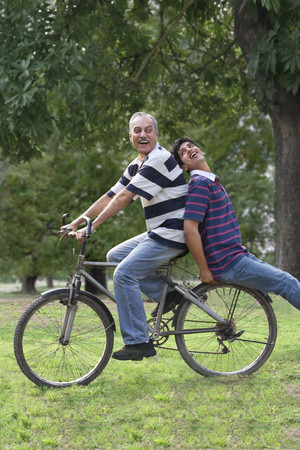 25 30: Father riding a bicycle while son sits behind