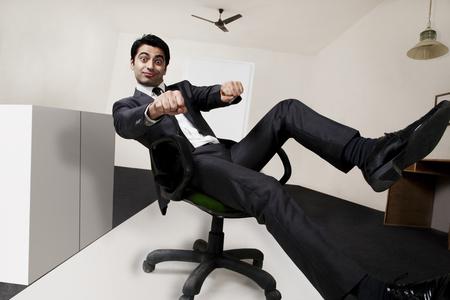 pretending: Businessman pretending to ride a motorbike in the office