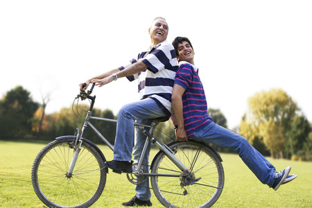 age 25 30 years: Father riding a bicycle while son sits behind