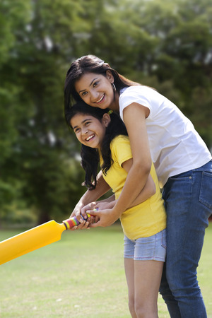 joyfulness: Mother and daughter playing cricket Stock Photo