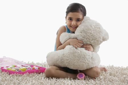 Girl hugging her teddy bear Imagens
