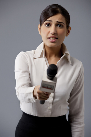 welldressed: Portrait of young woman news reporter holding out microphone