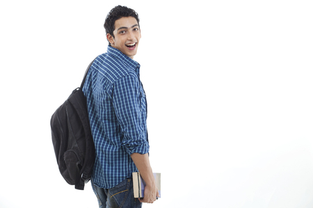 Cheerful young man with bag and book over white background